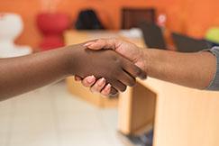 Contratação para farmácias: Mãos dadas do gestor de farmácia com o funcionário